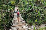 Backpacker on bBridge in tropical rainforest