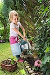 Girl gardening, watering flowers with scrutiny