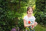 Girl in garden, cherries dangling from her ears
