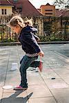 Blonde girl playing hopscotch on sidewalk, Munich, Bavaria, Germany
