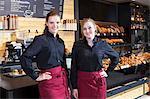 Female shop assistants in coffee shop standing side by side
