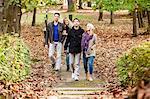Group of friends walking through autumn park