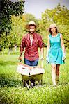 Young couple in vegetable garden, man pushing wheelbarrow