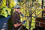 Man trimming plants by garden fence, Munich, Bavaria, Germany