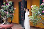 Woman wearing ao dai dress at Giac Lam Pagoda, Ho Chi Minh City, Vietnam, Indochina, Southeast Asia, Asia