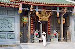 Woman wearing ao dai dress at Nghia An Hoi Quan Pagoda, Cholon, Ho Chi Minh City, Vietnam, Indochina, Southeast Asia, Asia