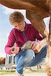 Woman cleaning horse's hoof, Bavaria, Germany
