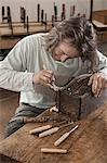 Carpenter restoring an antique bone box at workshop, Bavaria, Germany
