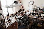 Senior male jeweler hitting punches in workshop, Bavaria, Germany