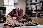 Senior female fashion designer checking fabric in workshop, Bavaria, Germany
