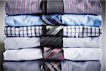Close-up of stack of dress shirts with ties, studio shot