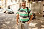 Portrait of mature man carrying skateboard, Rio De Janeiro, Brazil