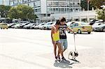 Young couple strolling with dog along sidewalk, Copacabana, Rio De Janeiro, Brazil