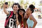 Three young adult friends posing for smartphone selfie, Copacabana, Rio De Janeiro, Brazil