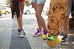Cropped shot of skateboarders legs on sidewalk, Copacabana, Rio De Janeiro, Brazil