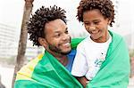 Father and son wrapped in Brazilian flag on Ipanema beach, Rio De Janeiro, Brazil