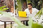 Man using laptop on patio