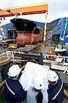 Workers looking at plans at shipyard, GoSeong-gun, South Korea