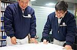 Workers looking at ship plans, GoSeong-gun, South Korea