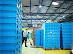 Worker arranging plastic crates in plastics factory