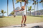Young woman skateboarding along pavement