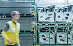 Worker passing car door parts in car factory