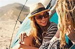 Girlfriends relaxing beside tent, Malibu, California, USA