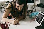 Female designer making note in design studio