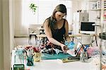 Female designer following instructions on digital tablet in design studio