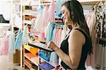 Female designer using touchscreen on digital tablet in design studio