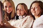 Three girls on sofa using digital tablet