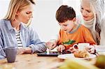 Three generation family using digital tablet