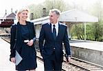 Businessman and woman talking on railway platform