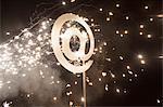 Illuminated at symbol with fireworks at night