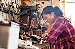 Female mechanic in workshop, using digital tablet, wearing earphones