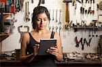 Female mechanic in workshop, using digital tablet