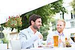 Happy businessmen having food at sidewalk cafe