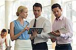 Businesswoman showing colleagues digital tablet