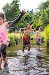 Children playing in a muddy creek