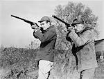1940s 1950s MEN YOUNG SENIOR WITH SHOT GUNS AIMING TOWARDS CAMERA WEARING HUNTING CLOTHES & HATS