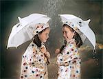 1960s SMILING TWIN GIRLS WEARING MATCHING POLKA DOT RAIN COATS AND HATS STANDING UNDER UMBRELLAS IN THE RAIN