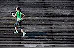 Female runner running up wooden stairway