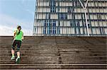 Female runner running up steep city stairway