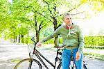Senior man leaning against bicycle, looking away