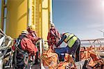 Engineers on boat preparing to climb wind turbine on offshore windfarm