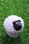 An Easter lamb cupcake on a grass surface