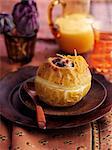 A baked apple with raisins, orange zest and vanilla sauce