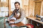 Portrait of leather craftsman at workshop bench