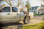 Handyman using smartphone on rear of truck