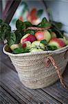 Apples in wicker bag on table